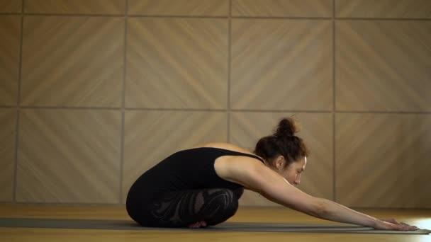 Mladá hezká žena cvičí jógu na lehkém minimalistickém ateliéru. Děvče se protahuje v sedě. Zdravotní životní styl koncept