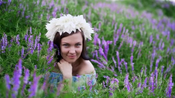 Beautiful woman with white flower wreath in violet field. Girl in blue dress smiling.