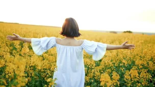 Žena s otevřenou náručí při západu slunce na řepkovém poli. Vděčnost, příroda, koncepce krásy.