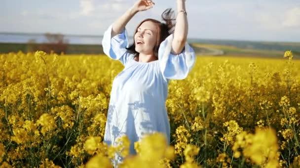 Mladá žena v šatech se raduje, otáčí se v řepkovém poli žlutých květin. Svoboda, láska, příroda.