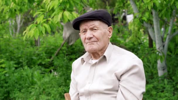 Very old caucasian man portrait. Grandfather in hat. Portrait: aged, elderly, loneliness, senior with lot of wrinkles on face. Close-up of a pensive old man sitting alone outdoors.