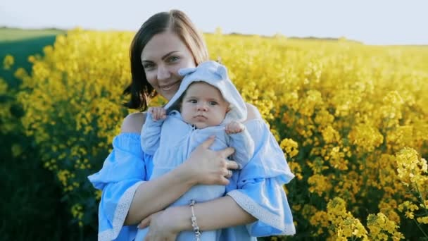 Portrait of young mother with newborn son having fun in yellow field. Love, family, joy concept.