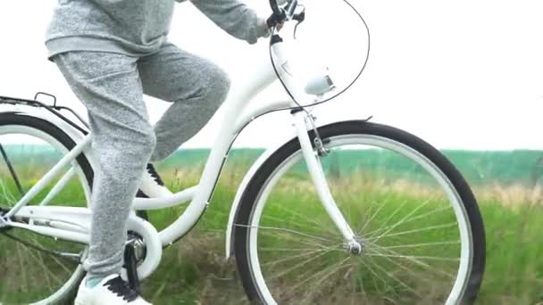 Legs of woman in white shoes riding retro bicycle countryside alone