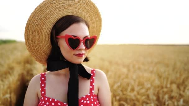 Portrét stylové ženy v pšeničném poli. Stará staromódní dívka v slaměném klobouku, srdeční brýle, červené polkové šaty a rtěnka. Cestování, móda, koncepce přírody