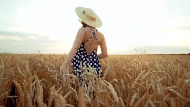 Unrecognizable defocused girl with straw hat walking in golden wheat field. Elegant sexy lady in long vintage dress. Golden hour. Harvest, travel concept.
