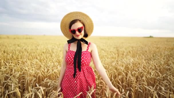 Portrait of stylish woman in wheat field. Old fashioned girl in straw hat, heart-shaped eyeglasses, red polka dot dress and lipstick. Travel, fashion, nature concept