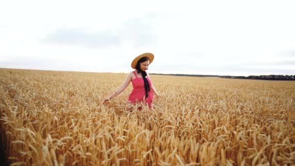 Beautiful woman in red dress and straw hat walking in golden wheat field. Beauty, nature, travel, harvest, harmony concept.