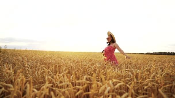 fröhliche Frau in rotem Kleid und Hut, die sich im goldenen Weizenfeld dreht und lächelt. Schönheit, Natur, Reisen, Ernte, Harmoniekonzept.