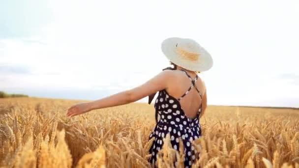 Retro oblečená dívka v slaměném klobouku a černých šatech, otáčející se na pšeničném poli během západu slunce. Radostná, veselá, šťastná žena.