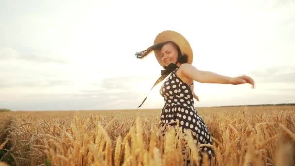 Retro gekleidetes Mädchen mit Strohhut und schwarzem Kleid, das sich bei Sonnenuntergang im Weizenfeld dreht. freudige, fröhliche, glückliche Frau.