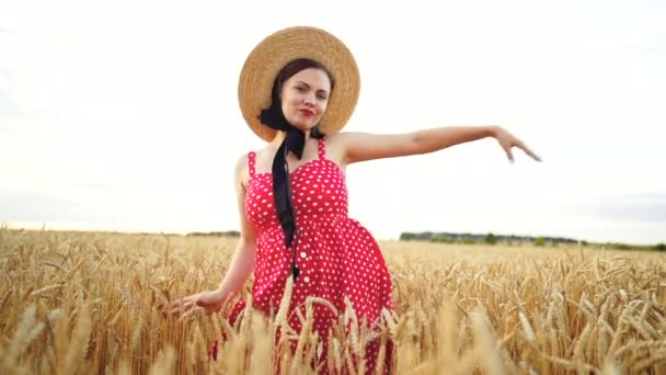 Attractive funny girl in red dress and straw hat dancing in golden wheat field. Success, retro style, joy, happiness concept