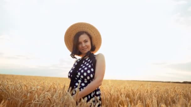 Joyful, cheerful, happy woman. Retro dressed girl in straw hat and black dress spinning around in wheat field during sunset.