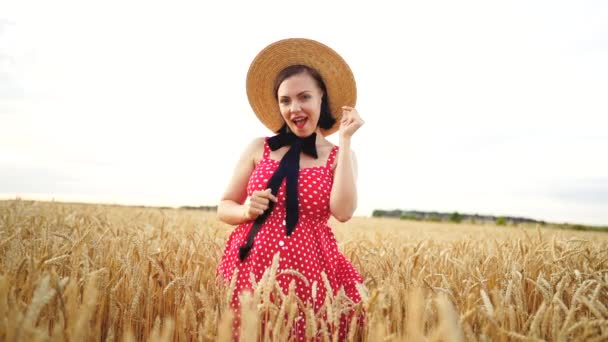 Pretty woman in red dress and straw hat funny dancing in golden wheat field. Old fashioned, retro, fun, happiness concept