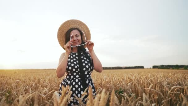 Portrét stylové ženy si klade sluneční brýle na pšeničný pole. Stará staromódní dívka v slaměném klobouku, černé polkové šaty. Cestování, móda, koncepce přírody
