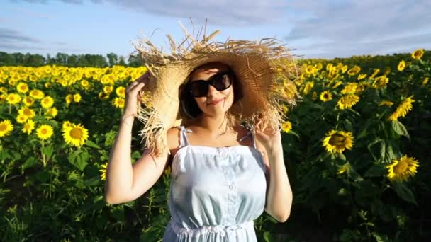 Young pretty woman in straw hat in sunflowers field looking to camera and smiling. Portrait of cute girl. Summertime. Slow motion.