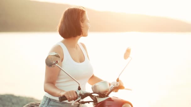 Cute girls portrait. Woman sitting on red retro motor bicycle at sunset river background. Cinematic vintage toned. Copy space