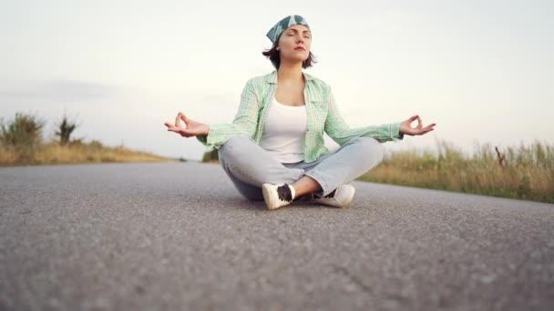 Mladá módní žena meditující v lotosové pozici a sedí na prázdné silnici mezi pouštními písky. Józa, náboženství, zenový koncept.