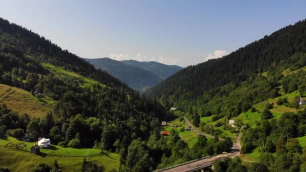 Aerial.Drone flies backward over stunning mountain nature.Carpathian mountains in Europe.View from height on village, developed infrastructure, bridge, road.