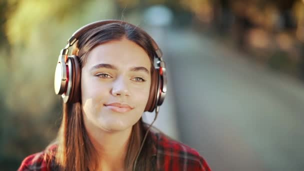 Young teenager listens to music through headphones in park.Girl in red plaid shirt smiles, dancing to rhythm.Concept of student life, freedom, modern youth