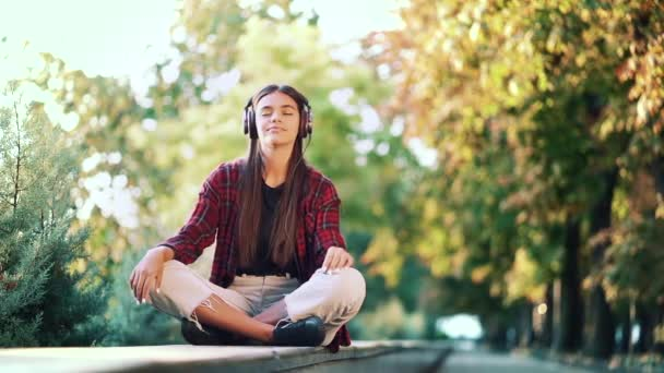 Portrait of attractive hipster dancing with earphones in park. Woman smiling. moves to the rhythm.Friendly appearance of modern trendy girl