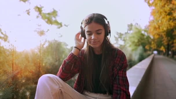 Fiatal tizenéves zenét hallgat a fejhallgatón keresztül a parkban.Lány piros kockás ing mosolyog, táncol a ritmusra.Fogalom a diákélet, a szabadság, a modern ifjúság
