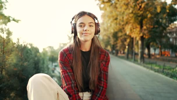 Portrait of attractive girl dancing with earphones in park. Woman smiling. moves to the rhythm.Friendly appearance of modern trendy hipster