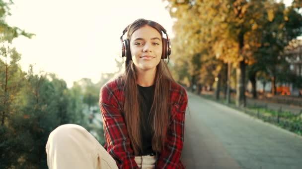 Porträt eines attraktiven Mädchens, das mit Kopfhörern im Park tanzt. Frau lächelt. bewegt sich im Rhythmus. Freundliches Auftreten moderner trendiger Hipster