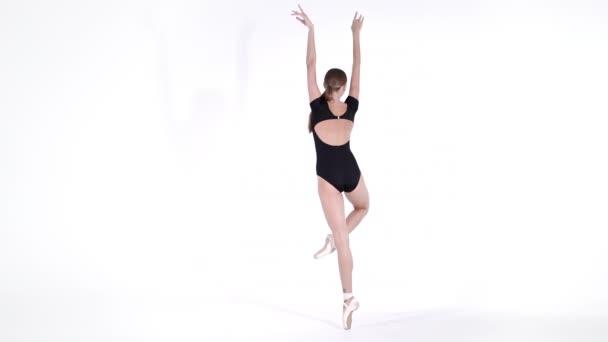 professionelle Ballerina Ballett auf weißem cyclorama.beautiful junges Mädchen mit langen Haaren trägt schwarzen Anzug isoliert auf weißem Studiohintergrund.