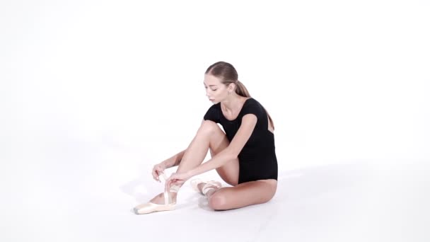 Ballerina wraps white silk ribbons of soft top ballet shoes pointe and ties them up. Woman preparing for dance training lessons in gym.