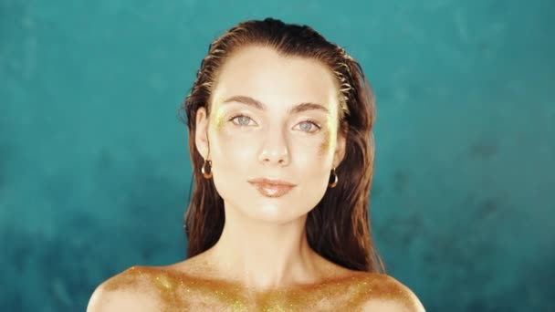 Portré csillogó nő arany test művészet a kék háttér. Divatos lány tökéletes egészséges bőrrel. Művészet, nőiesség fogalma.