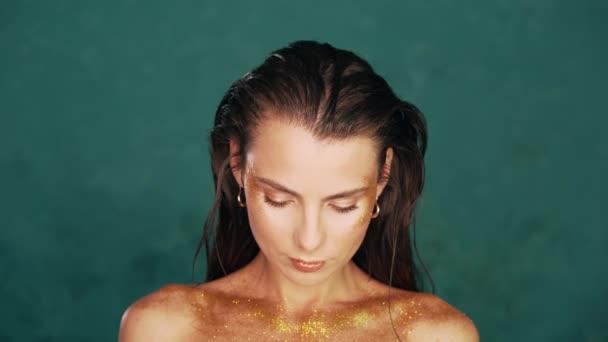 Úžasný smyslný modelka dívka close-up portrét v tyrkysovém studiu. Zlatý make-up, vizáž, koncepce tělesného umění.