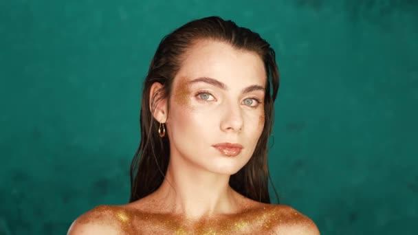 Luxusní zlatý make-up na hezké ženě s modrýma očima. Ozdoba těla, módní model ve studiu s dokonalým světlem na tyrkysovém pozadí