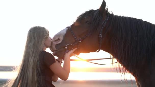 Fiatal szőke lány hosszú hajjal simogatja és csókolgatja a lovat. Lassú mozgás. Gyönyörű fiatal nő, sötét csődörrel a természetben. Szerelem és barátság fogalma.