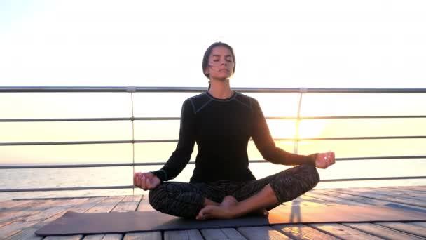 Konzentriertes Mädchen in Schwarz praktiziert Yoga-Meditation an der hölzernen Strandpromenade. Frau in Lotuspose. Dehnen, üben, gesundes Lebensstilkonzept