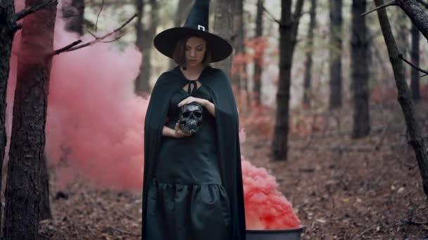 schwarze Hexe mit Totenkopf in den Händen, streichelnd auf Herbstdunst-Waldhintergrund. Horror, Halloween, Cosplay-Urlaub, magisches Konzept