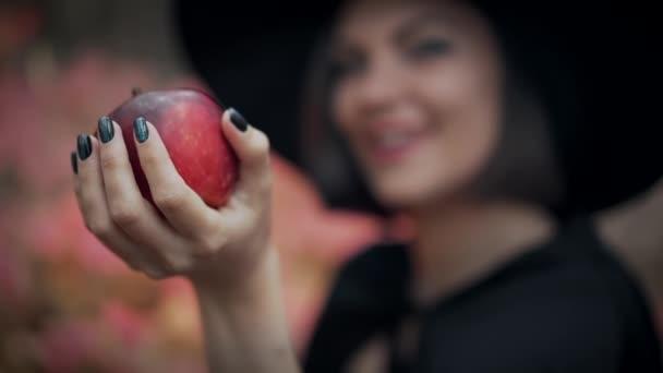 Žena jako čarodějnice se zlým úsměvem v černém nabízí červené jablko jako symbol pokušení, jed. Pohádkový koncept, halloween, cosplay.