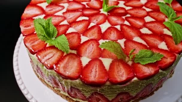Csodálatos gyönyörű kézzel díszített házi eper Fraisier torta forog. Ízletes, friss, étvágygerjesztő desszert közelről mentás spriggel. Cukrászati művészet, maximalizmus az élelmiszer-koncepcióban.