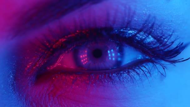 Extrémní blízkost lidské oční duhovky pod neonovým světlem 4K. Žena s krásným make-upem, třpytivými stíny a falešnými řasami. Ženské zelené oči se stahují. Noční život, noční klub koncept.