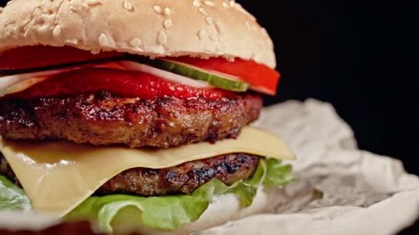 Mňam hamburger, rychlá občerstvení. Čerstvý domácí grilovaný burger s masovou plackou, rajčaty, okurkou, salátem, cibulí a sezamovými semínky. Nezdravý životní styl. Pozadí jídla. 4k