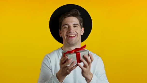 Hezký hipster muž drží vánoční dárek a dává ho rukou na kameru. Je šťastný, usmívá se. Chlápek v klobouku na žlutém pozadí. Pozitivní vánoční záběry.
