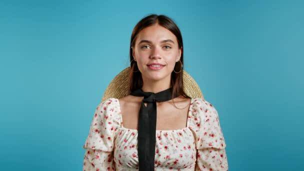 Mladá žena v květinových šatech a slamáku hledí do kamery. Portrét flirtování krásná dívka na modrém pozadí stěny studio.