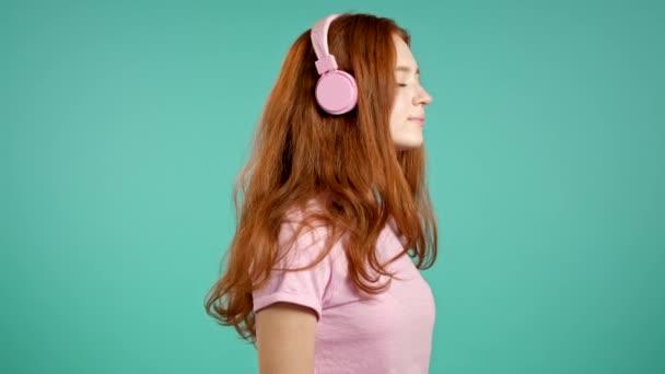 Hübsches junges Mädchen mit langen Haaren hört Musik, lächelt, tanzt mit Kopf und Kopfhörer im Studio vor blauem Hintergrund. Musik, Tanz, Radiokonzept, Zeitlupe