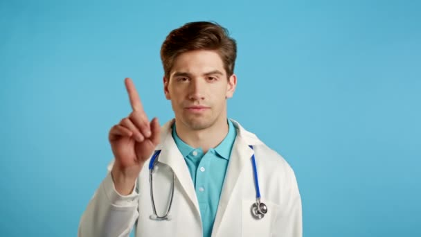 Portrait of serious doctor in professional medical white coat showing rejecting gesture disapproving with no finger sign. Denying, Disagree. Doc man isolated on blue background.