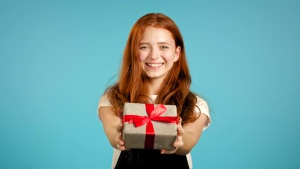 Roztomilá mladá žena v celkovém držení dárkové krabice a dává ji rukou na kameru na modrém pozadí zdi. Dívka se usmívá, je šťastná.