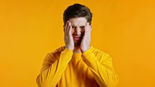 Junger Mann mit Kopfschmerzen, Studioporträt. Guy legt die Hände auf den Kopf, isoliert auf gelbem Hintergrund. Problembegriff, Medizin, Krankheit