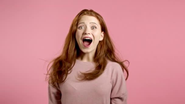 Frau zeigt Erstaunen, zeigt WOW Entzückung Gesichtseffekt. Überrascht aufgeregtes, glückliches Mädchen. Hübsche weibliche schockiert Modell auf rosa Hintergrund.