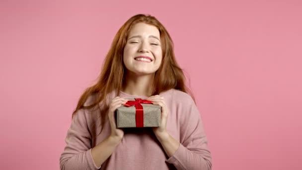 Aranyos fiatal nő kezében ajándék doboz íj, kíváncsi, mi van benne. Rózsaszín fal háttér. A lány mosolyog, örül, hogy ajándékot kap..