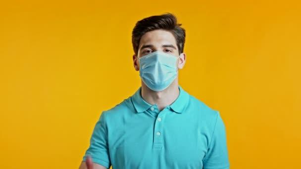 Hezký mladý muž v ochranné lékařské masce se usmívá před kamerou. Chlápek ukazující palce nahoru, jako cedule na žlutém pozadí. Vítěz. Úspěch. Jazyk těla.