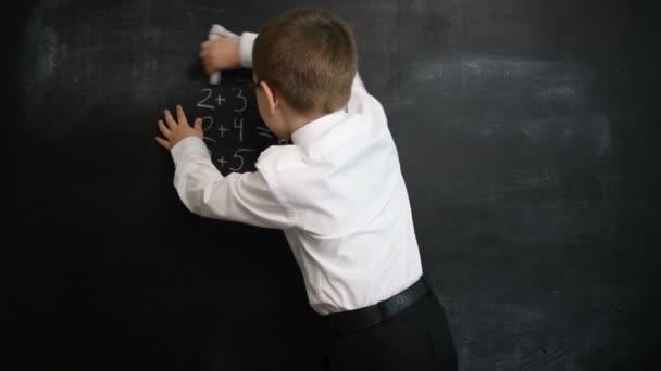 Fiatal fiú mosás tábla után megoldása a matematikai kifejezések. Kreatív koncepció vissza az iskolába és a tanulmány. Iskola előtti