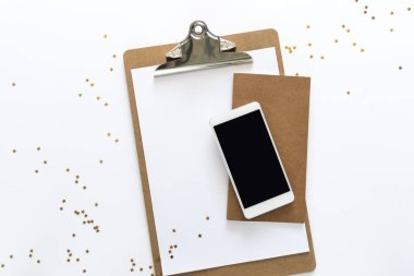 Top view over the working desk with paper, notebook and phone at the top with randomly droped golden stars. Copy space for text. Flat lay of a workplace on white background.